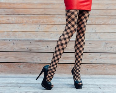 A young woman with long legs in fishnet stockings