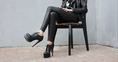 woman posing in tight black pants and super high boots on laces sitting on a studio in the street
